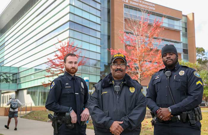 A new UA Little Rock Campus Police community liaison officer program is headed up by Assistant Police Chief Benjamin Rommel, center. Patrolmen Gavin Hurst, left, will serve as a community liaison officer, while Corp. Gary McGee, right, will serve as the campus housing liaison officer. Photo by Ben Krain.