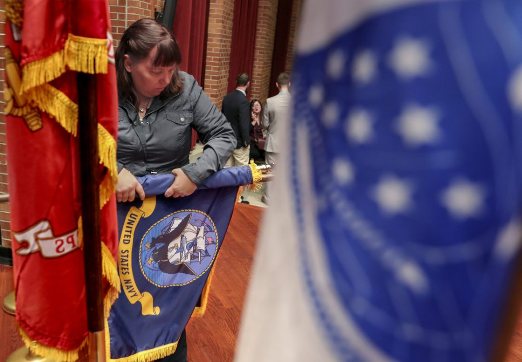 Military Student Success Center Assistant Director and Coast Guard veteran Cheryl Kleeman prepares flags for the Nov. 12 ceremony.