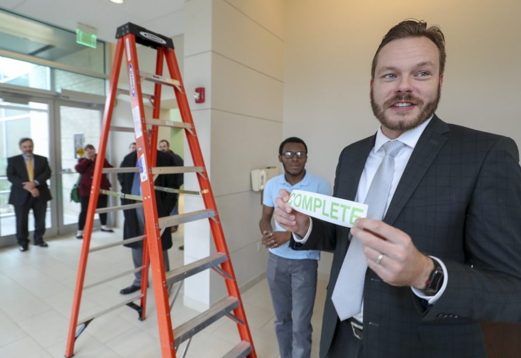 Thomas Bunton, UA Little Rock director of Technology Infrastructure and Operations, holds a sign marking the completion of a campus wide networking system upgrade after installing the last piece of equipment in the Center for Integrative Nanotechnology Sciences. Photo by Ben Krain