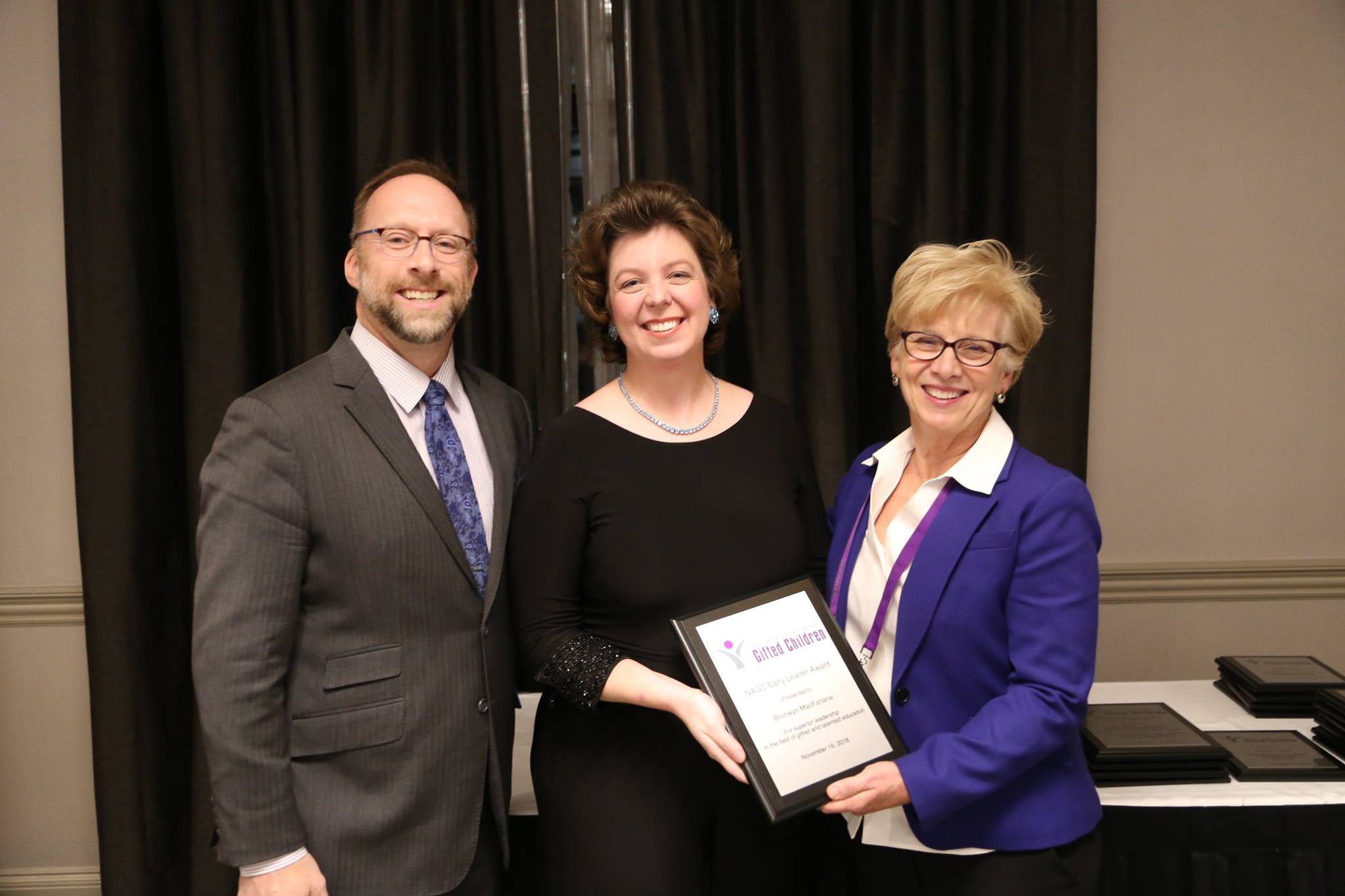 Dr. Bronwyn MacFarlane (middle) recieves the 2019-19 Early Leader award from Dr. Jonathon Plucker (left), NAGC president-elect and rofessor at Johns Hopkins University, and Dr. Sally Krisel, NAGC president and faculty at University of Georgia, at the 65th Annual Convention Celebration of Excellence Awards Ceremony of the National Association for Gifted Children.