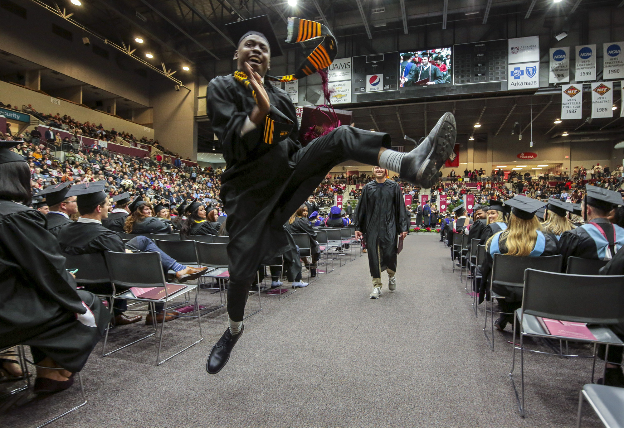 A UA Little Rock student leaps in the air to celebrate his graduation in December 2018.