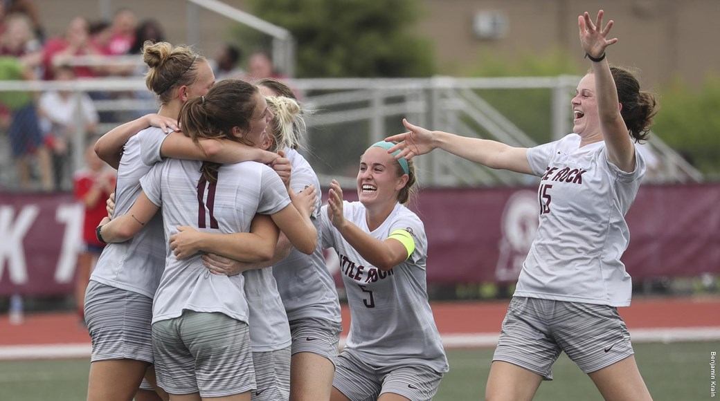 UA Little Rock women's soccer team members celebrate after scoring a goal.