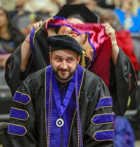 UA Little Rock criminal justice doctoral student Marc Glidden, a visiting assistant professor of criminal justice, is hooded during the May 11 graduation ceremony. Photo by Ben Krain.
