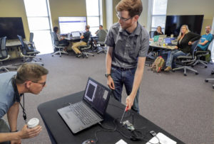 Philip Huff (right), UA Little Rock assistant professor and research fellow at Emerging Analytics Center, leads a cybersecurity workshop for high achool teachers from around the state. Photo by Ben Krain.