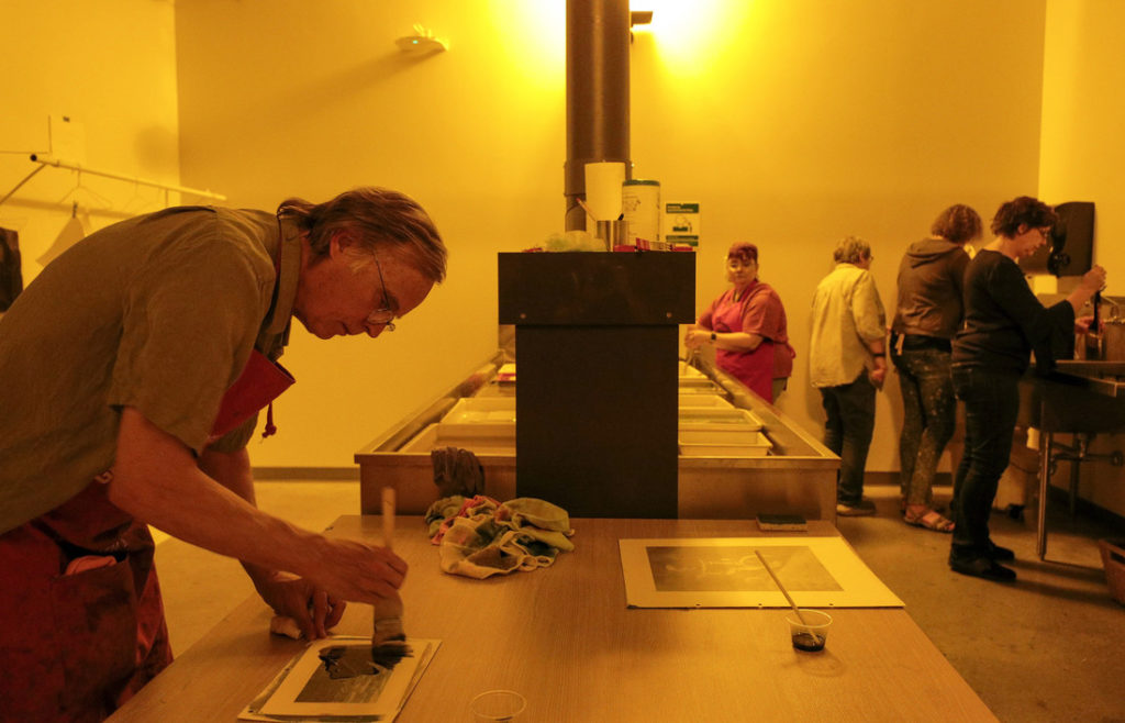 Workshop participants develop photographs in a darkroom at the Windgate Center of Art and Design using a 19th-century photographic process. Photo by Ben Krain.