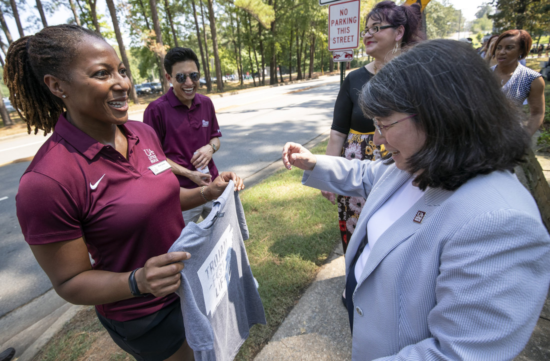 Chancellor Christina Drale (right) receives a t-shirt from Kristi Smith at BBQ at Bailey. Photo by Ben Krain.