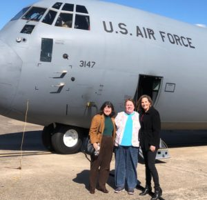 Chancellor Christina Drale (left), Kathy Oliverio (middle), and Edie Stewart (right) stand in from of the C-130 military aircraft before departure.