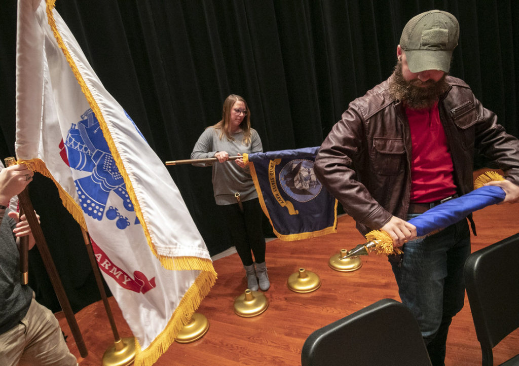 UA Little Rock student veterans, Kaycee Greenwood, US Air Force Reserve, center, and Sean Lewis, US Marine Corps., right, participate in a Veterans Day ceremony held in the Stella Boyle Smith Auditorium. Photo by Ben Krain
