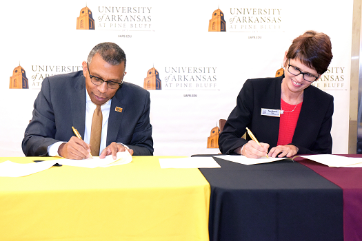 UAPB Chancellor Laurence Alexander (left) and Bowen Dean Theresa Beiner (right) sign an agreement to create a 4+3 pipeline agreement between the schools. Photo by Richard Redus.