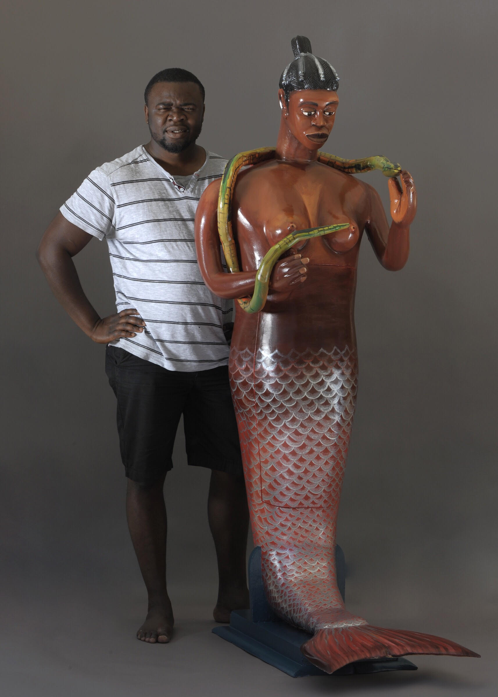 "Eric Adjetey Anang stands in front of one of his coffins that will be featured in the exhibit ""Celebrating Death: Fantasy Coffins of Ghana."""