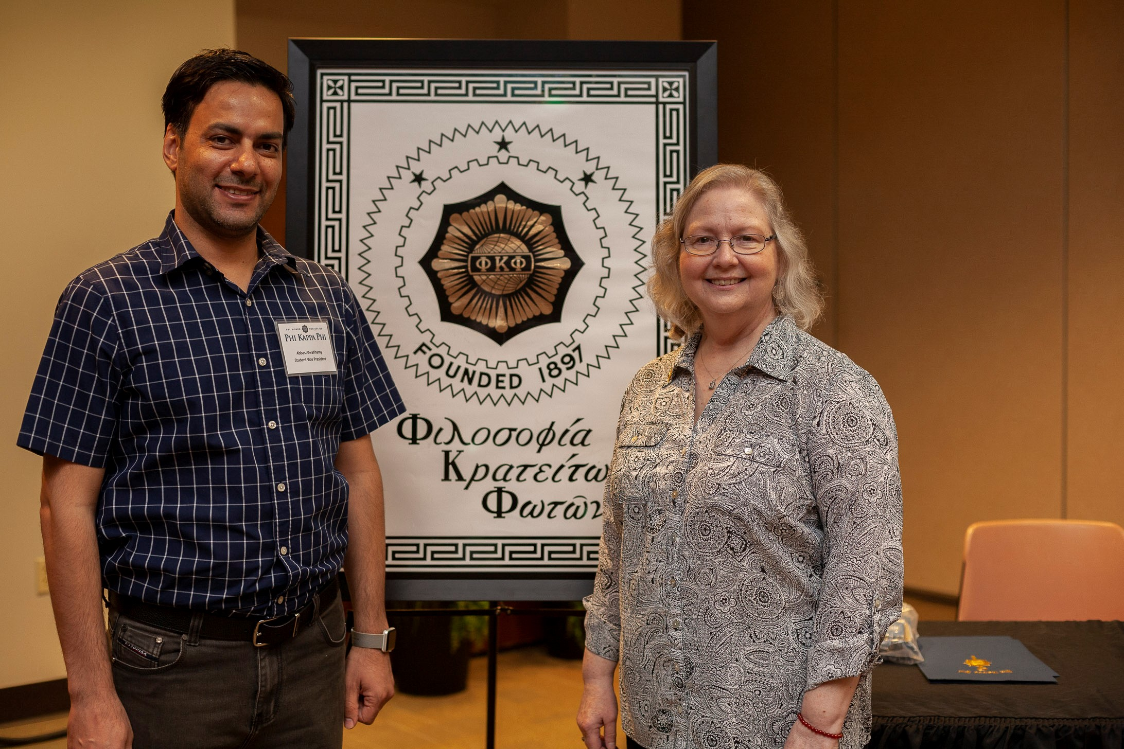 Phi Kappa Alpha Administrative Liaison-Linda Stipsky talks with Phi Kappa Alpha Vice President Abbas Al-Wahhamy during the 2019 induction ceremony.