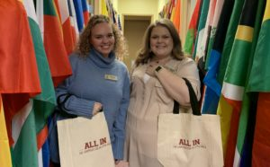 Study Abroad staff members Leslie Parker, left, and Emily Bell, right, receive tote bags after donating to the Campus Campaign.