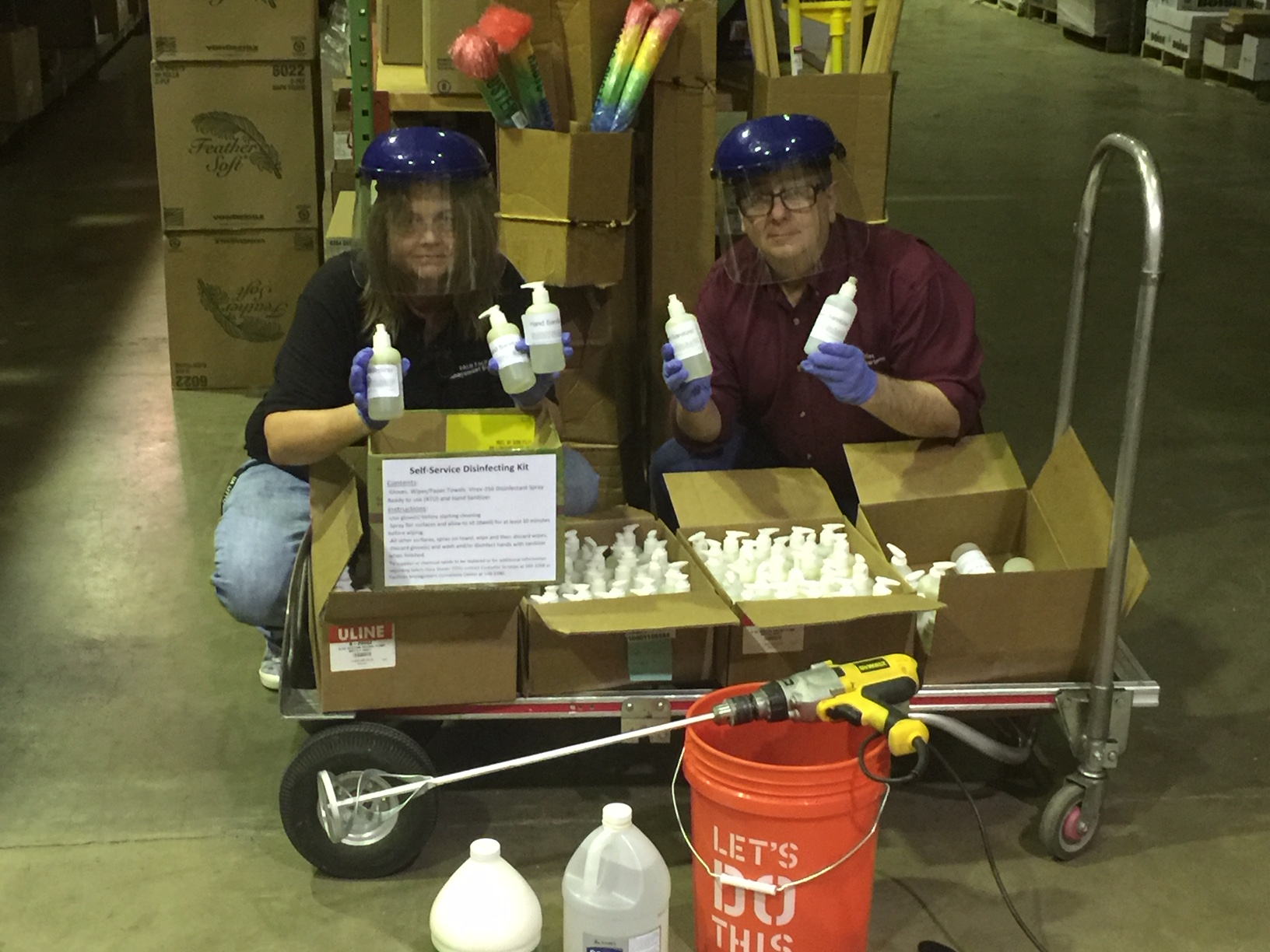 Sandra Vail, left, and Vince Rodgers, right, transport the hand sanitizers made by Facilities Management for use on the UA Little Rock campus.