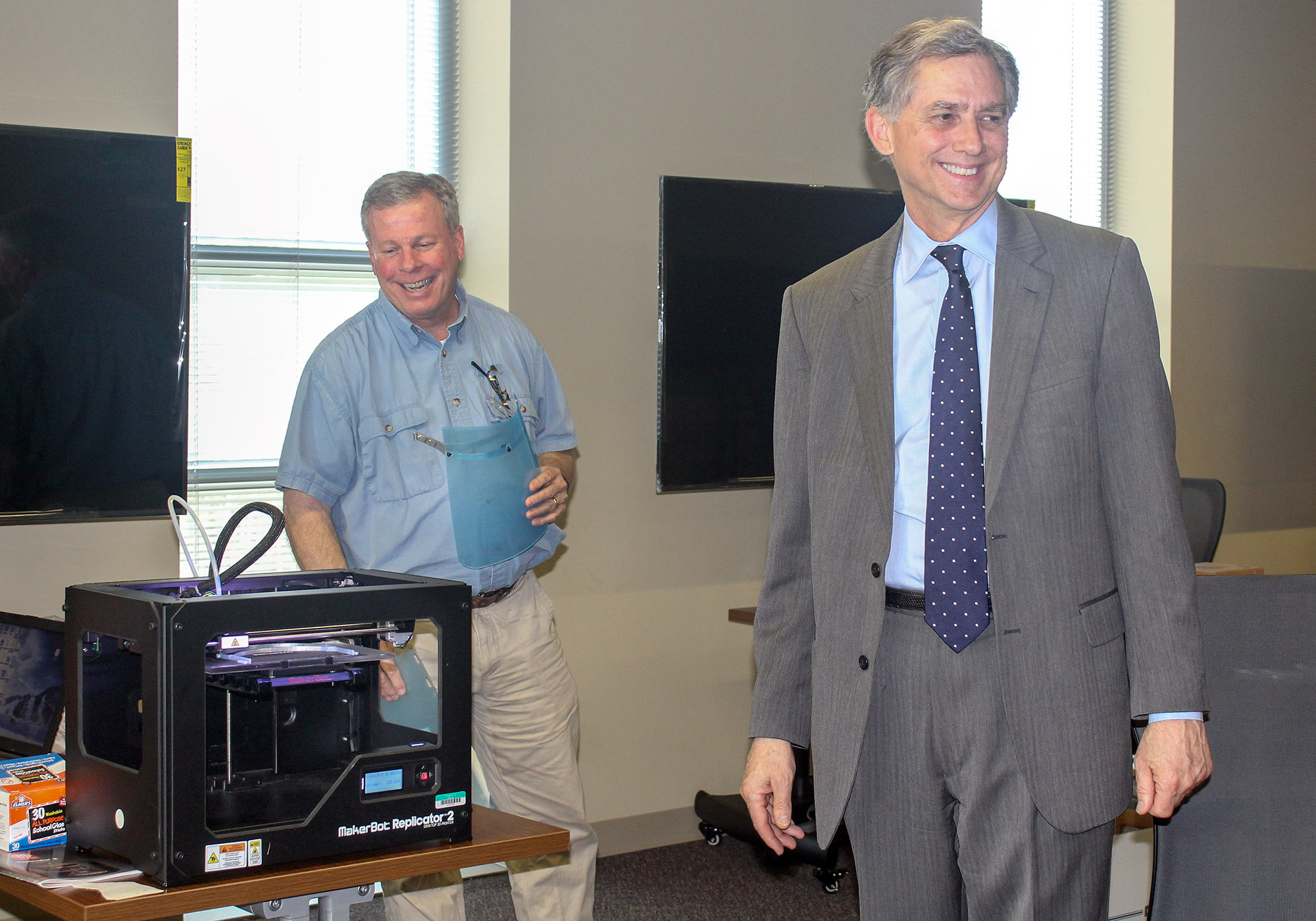 Jay Chesshir (left), president and CEO of the Little Rock Regional Chamber of Commerce, and U.S. Rep. French Hill (right) inspect the 3D printers that are printing face shields for CHI St. Vincent. Photo by Angie Faller.
