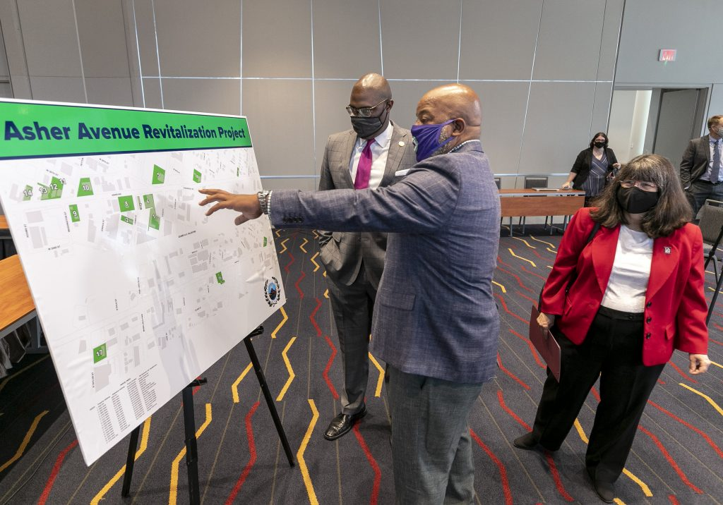UA Little Rock Chancellor Christina Drale (right), Mayor Frank Scott Jr. (left), and business owner Tracy Johnson (center) review plans for revitalization efforts along Asher Avenue during a Sept. 2 press conference at Robinson Hall. Photo by Ben Krain.