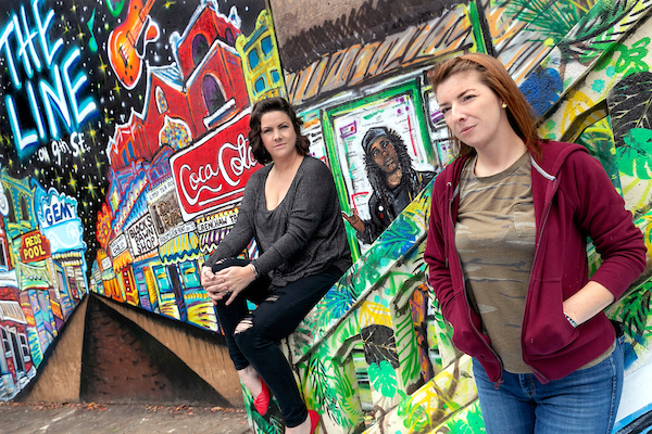 UA Little Rock students Nicole Stewart, left, and Talia Winkler are contributing their artistic talent to paintings on the 7th Street Peace Mural in Little Rock. Photo by Ben Krain.