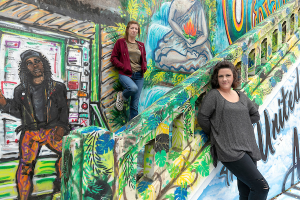 UA Little Rock students Talia Winkler, center, and Nicole Stewart, right, are contributing their artistic talent to paintings on the 7th Street Peace Mural in Little Rock. Photo by Ben Krain.