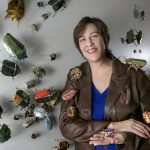Joli Livaudais with her installation of paper beetles on display in the Windgate Center.