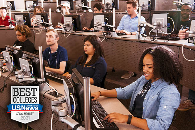 "Students sit at computers in a campus computer lab, engaged in their work. A badge on the image says, ""U.S. News Best Colleges 2021: Social Mobility."""