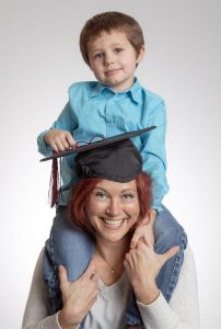 UA Little Rock first-generation student and single mom Erin Clement tries on her graduation cap with her son Ehren. Photo by Ben Krain.