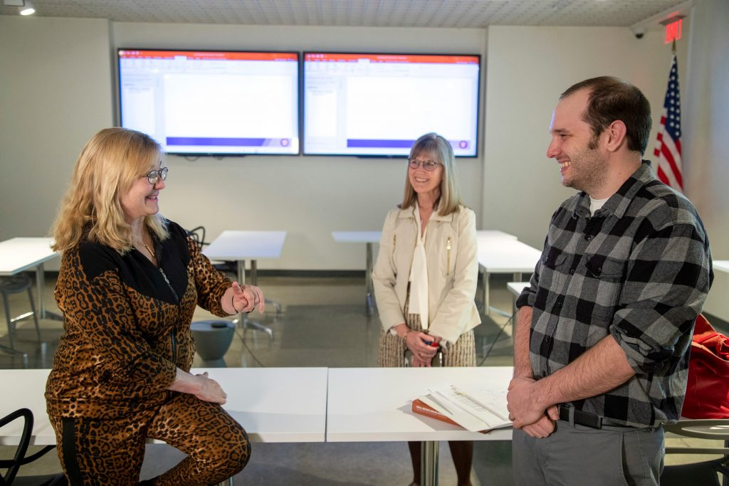 Leslye Shellam, left, daughter of L. Dickson Flake, talks with UA Little Rock business student Stephen Malec, right, and Elizabeth Small, center, primary instructor for the UA Little Rock Real Estate program. Malec is the first student to receive the new L. Dickson Flake Endowed Scholarship. Photo by Ben Krain.