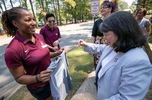 Kristi Smith presents a t-shirt to Chancellor Christina Drale during the 2019 BBQ at Baileys event. Photo by Ben Krain.