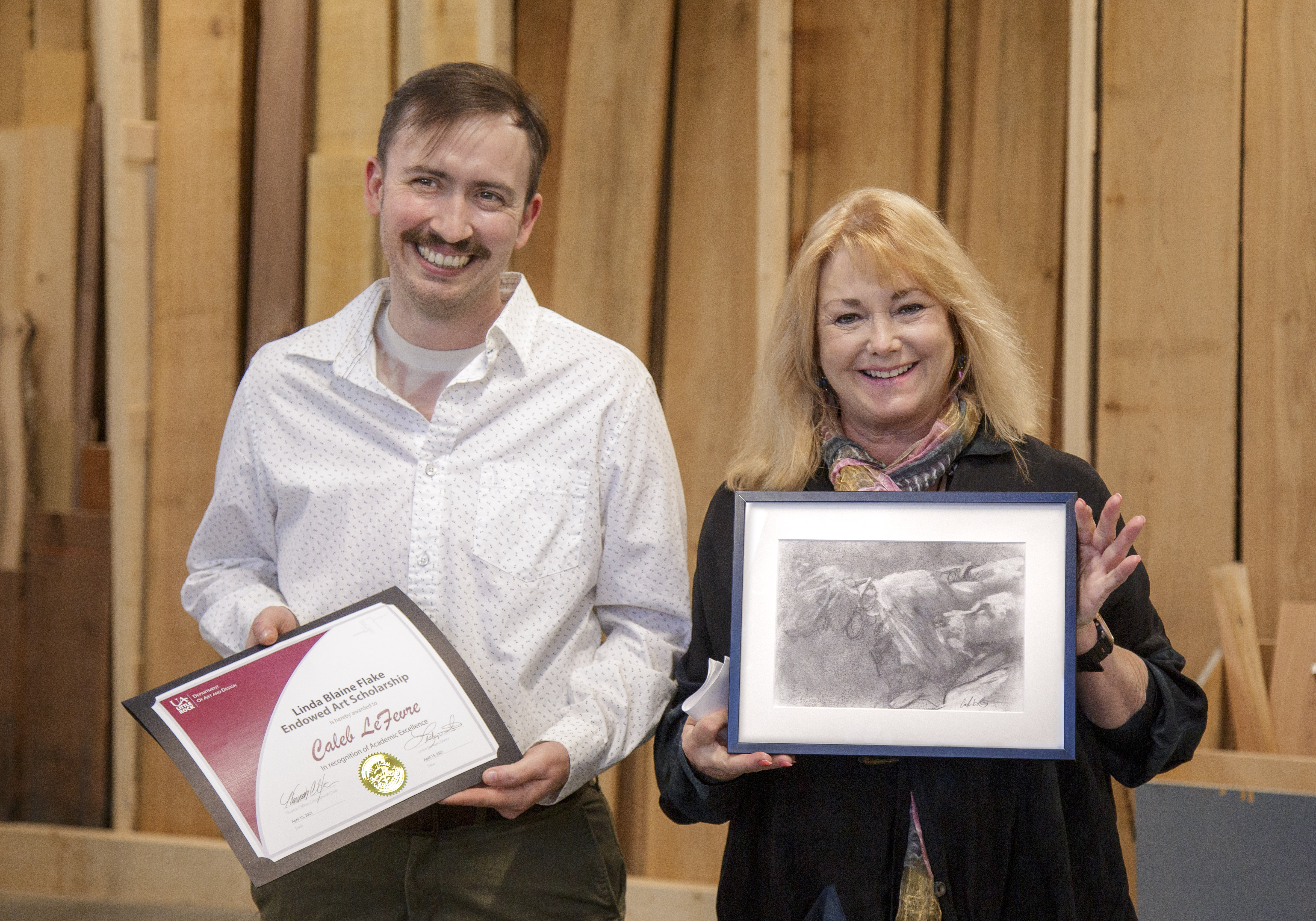 UA Little Rock studio art major Caleb LeFevre, left, was awarded the Linda Blaine Flake Endowed Art Scholarship by philanthropist Lesley Shallom during an event at the Windgate Center for Art + Design in celebration of World Art Day. Shellam is holding one of LeFevre's charcoal art works.