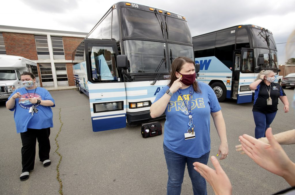 Jennifer Blanks, center, communicates in sign language to other staff members at the Arkansas School for the Deaf about boarding students onto buses before the school's weekend dismissal. Photo by Ben Krain.