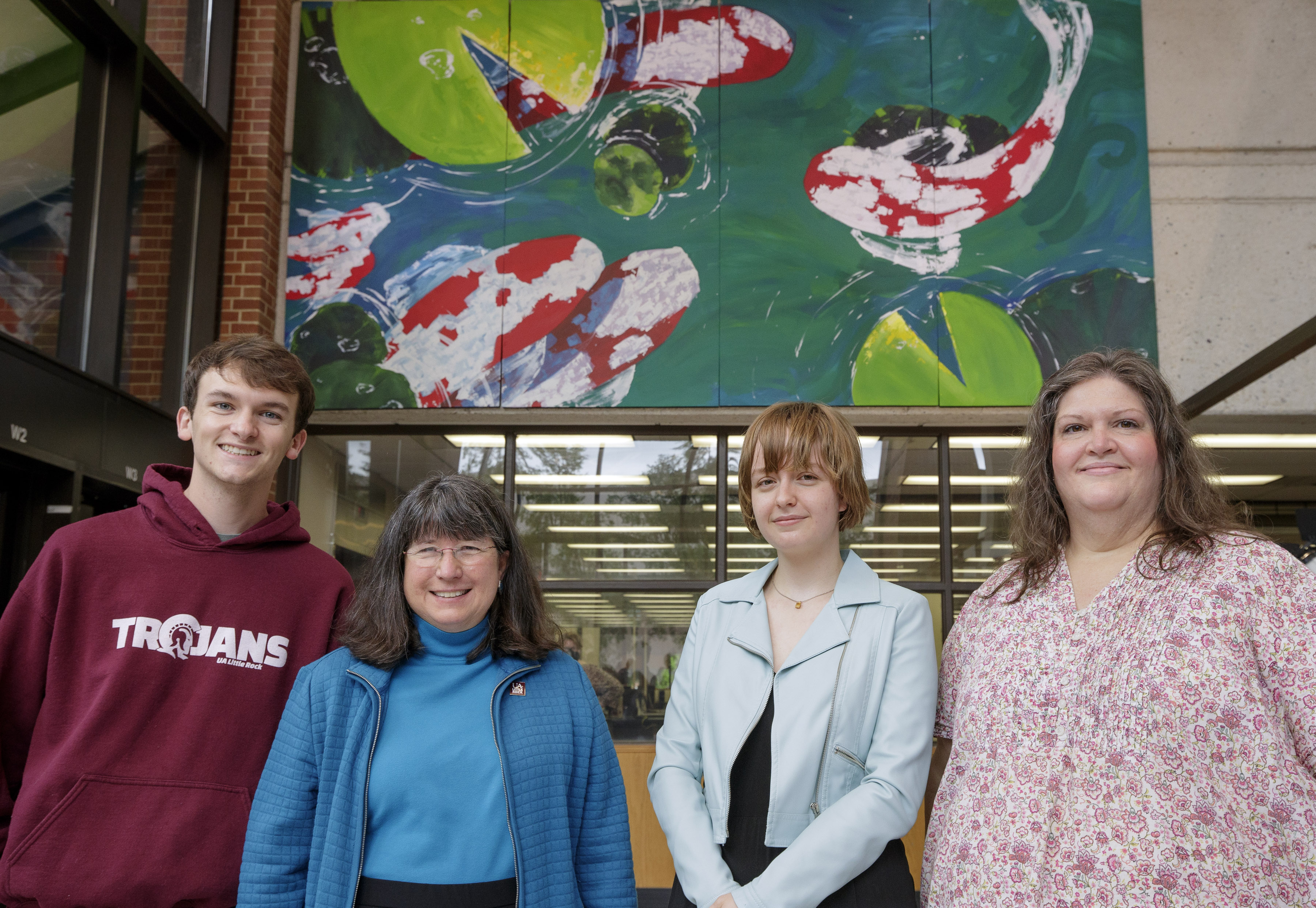 UA Little Rock student artist Emma Chambers, center right, poses in front of her winning mural with Student Government Association president Landon McKay, left, Chancellor Christy Drale center left, and Nancy Hamilton, Faculty Senate Building and Grounds committee member, far right, during a dedication ceremony for the mural at the Ottenheimer Library on campus. Chambers, a junior Bachelor of Fine Arts major with a concentration in painting, won the first student mural competition at the University of Arkansas at Little Rock. The Student Government Association, in conjunction with the Faculty Senate Building and Grounds committee, created the mural contest open to all UA Little Rock students. Chambers received more than 750 votes and $1000 for her design of swimming koi fish.