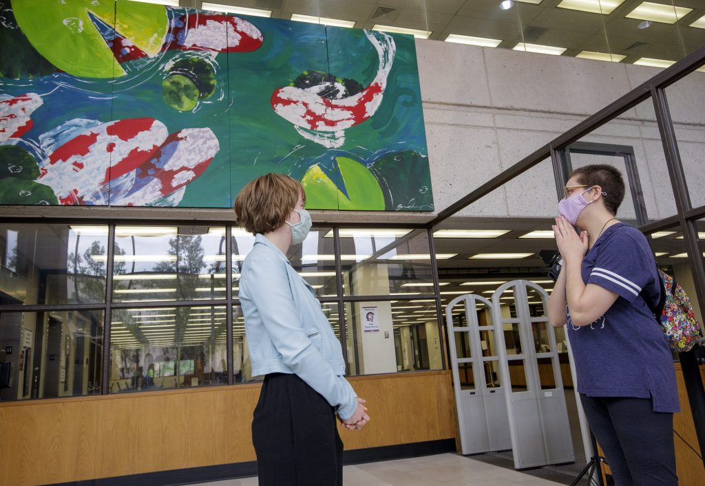 UA Little Rock student artist Emma Chambers, left, is congratulated by her friend during a dedication ceremony for the mural at the Ottenheimer Library on campus. Photo by Ben Krain.