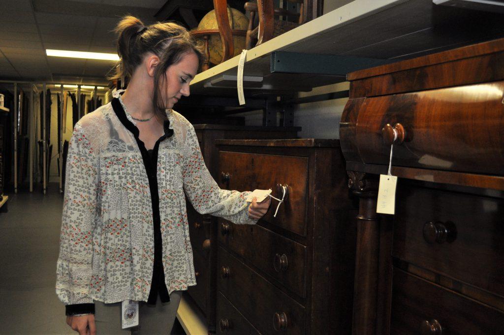 Jordan Hancock examines items in Historic Arkansas Museum's collection.