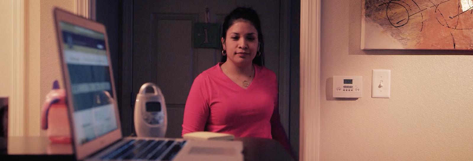 Woman walks from dim hallway toward her laptop.
