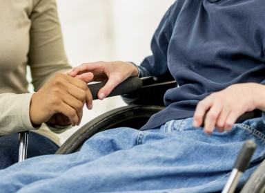 hands of social worker on wheelchair of boy with developmental disability