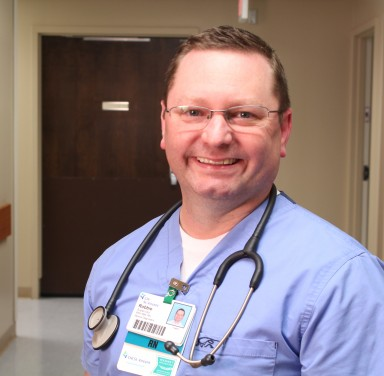 Male nurse Robbie Hemmer stands in a hospital hallway, smiling at the camera.