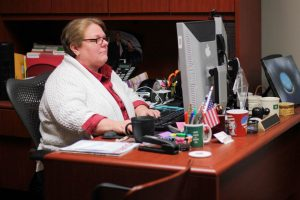 Kathy Oliverio working at her desk