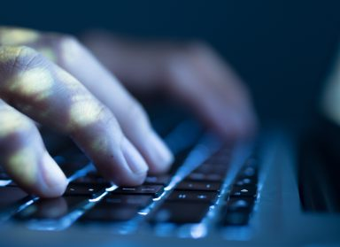 Close-up image of software engineer typing on laptop
