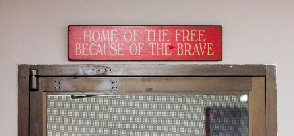 """Sign saying 'Home of the free because of the brave"""" above door"""