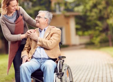 senior man in wheelchair with happy caregiver daughter