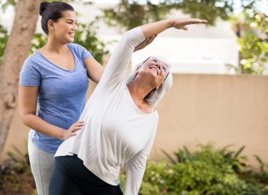 Smiling trainer instructing senior woman while exercising