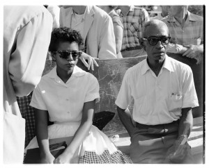 Elizabeth Eckford and L.C. Bates sit on a bench outside of Little Rock Central High School, 1957