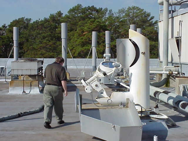 A faculty member inspects the Heliostat on the roof of Friborough hall