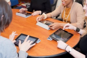 A photo of writers around a conference table working with iPads