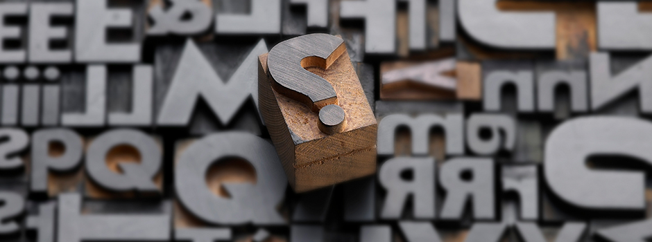 Photo of randomly arranged letterpress wooden letters with a question mark sitting on top.
