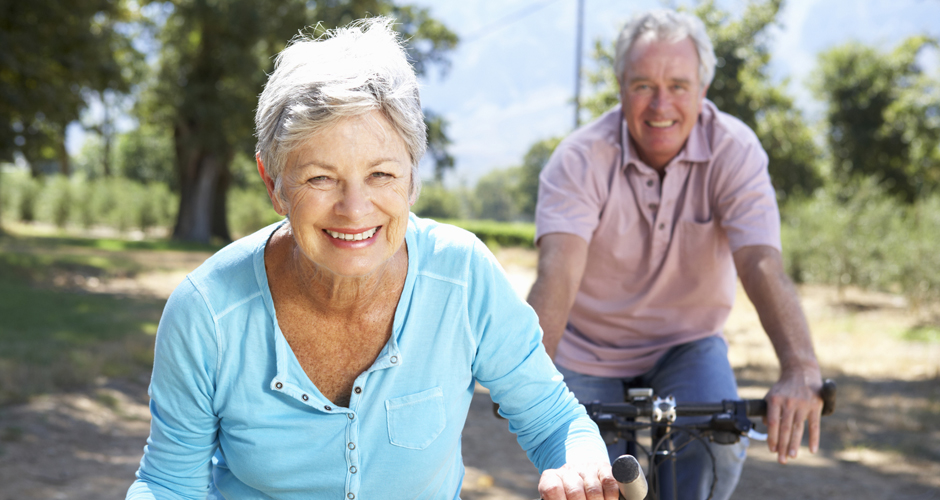 Elderly couple riding on bicycles.