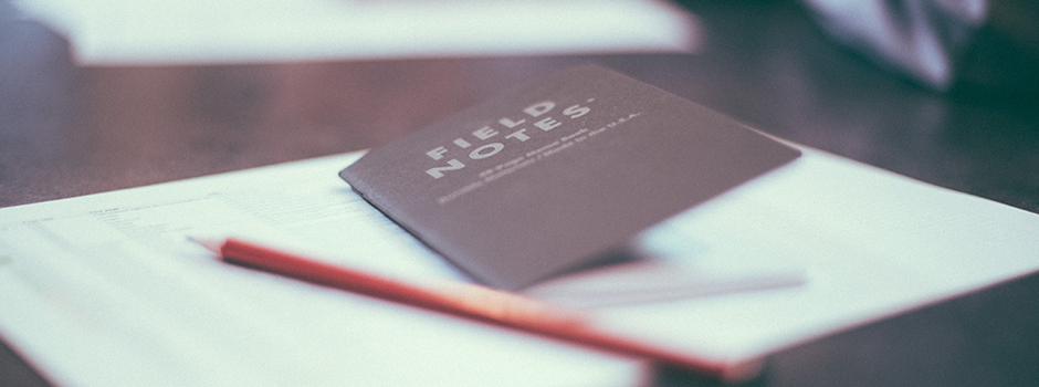 Field Notes pocket notebook laying next to a pencil on a table.