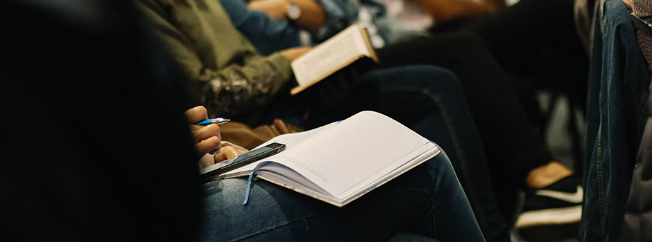 Students taking notes in a auditorium classroom.