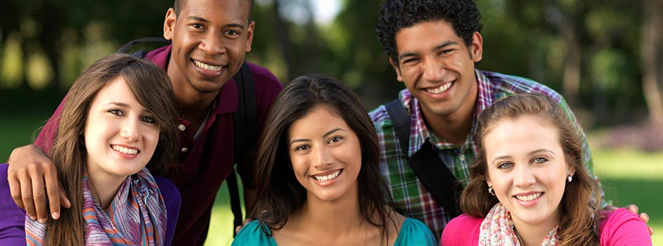 A group of smiling students in a park.