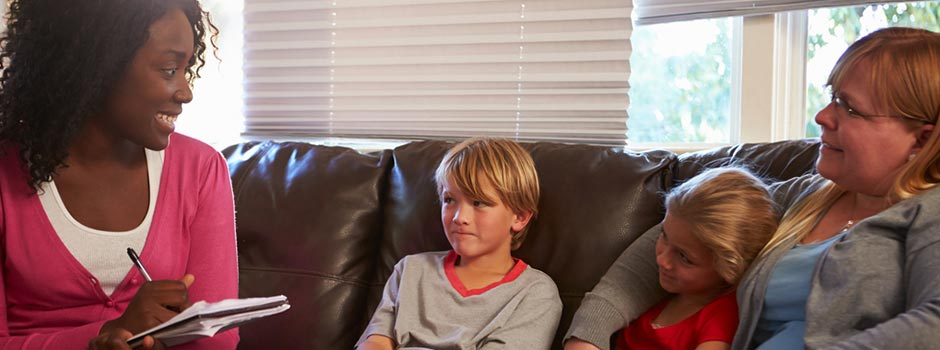 Social worker sitting with a woman and her two children on a leather couch.