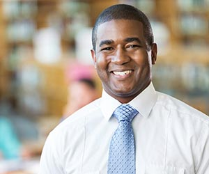 African American male in business attire smiling at the camera.