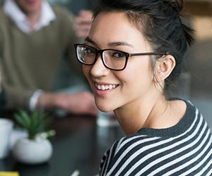 Young Asian female with black rimmed glasses smiles at the camera while sitting at a table with other students.